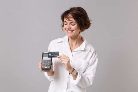 Smiling young business woman in white shirt posing isolated on grey background. Achievement career wealth business concept. Hold modern bank payment terminal to process acquire credit card payments. Stock fotó