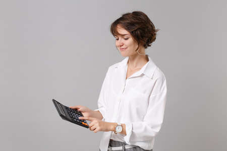 Smiling attractive young business woman in white shirt posing isolated on grey wall background studio portrait. Achievement career wealth business concept. Mock up copy space. Hold in hand calculator.