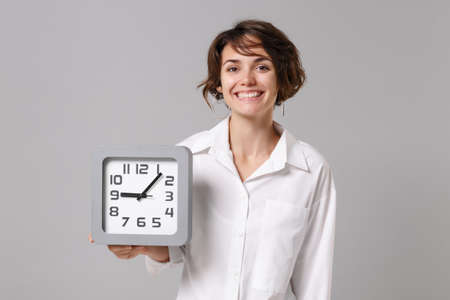Cheerful pretty young business woman in white shirt posing isolated on grey wall background studio portrait. Achievement career wealth business concept. Mock up copy space. Holding in hand clock.