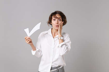 Amazed young business woman in white shirt posing isolated on grey background studio portrait. Achievement career wealth business concept. Mock up copy space. Hold paper check mark, put hand on cheek.