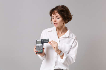 Beautiful young business woman in white shirt posing isolated on grey background. Achievement career wealth business concept. Hold modern bank payment terminal to process acquire credit card payments.