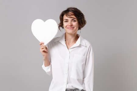 Smiling beautiful young business woman in white shirt posing isolated on grey wall background studio portrait. Like blogging social network concept. Mock up copy space. Hold white blank empty heart. Stock fotó