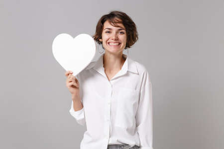 Funny attractive young business woman in white shirt posing isolated on grey wall background studio portrait. Like blogging social network concept. Mock up copy space. Hold white blank empty heart.