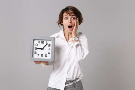 Shocked young business woman in white shirt posing isolated on grey wall background studio portrait. Achievement career wealth business concept. Mock up copy space. Hold clock, put hand on cheek.