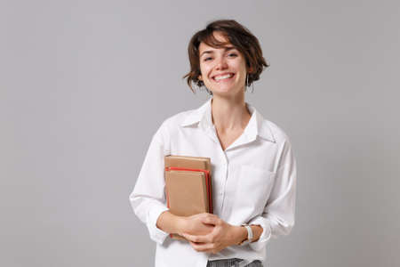 Cheerful pretty young business woman in white shirt posing isolated on grey wall background studio portrait. Achievement career wealth business concept. Mock up copy space. Holding books, notebooks.