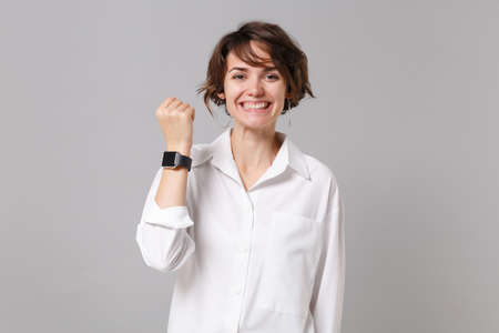 Smiling funny young business woman in white shirt posing isolated on grey wall background studio portrait. Achievement career wealth business concept. Mock up copy space. Wearing smart watch on hand.