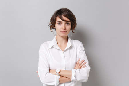 Beautiful young business woman in white shirt posing isolated on grey background studio portrait. Achievement career wealth business concept. Mock up copy space. Holding hands crossed, looking camera. Archivio Fotografico
