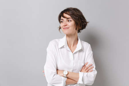 Smiling young business woman in white shirt posing isolated on grey background studio portrait. Achievement career wealth business concept. Mock up copy space. Holding hands crossed, looking aside.