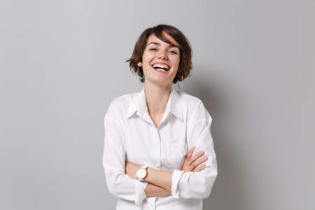 Laughing young business woman in white shirt posing isolated on grey background studio portrait. Achievement career wealth business concept. Mock up copy space. Holding hands crossed, looking camera.
