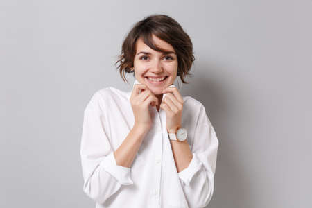 Cheerful pretty young business woman in white shirt posing isolated on grey wall background studio portrait. Achievement career wealth business concept. Mock up copy space. Straightening collar.