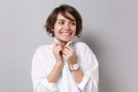 Smiling young business woman in white shirt posing isolated on grey wall background studio portrait. Achievement career wealth business concept. Mock up copy space. Straightening collar looking aside.