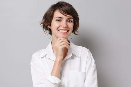 Charming young business woman in white shirt posing isolated on grey wall background in studio. Achievement career wealth business concept. Mock up copy space. Put hand prop up on chin looking camera.