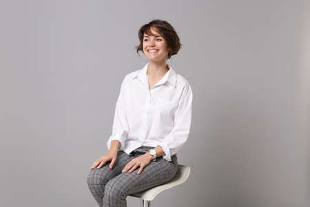 Cheerful funny young business woman in white shirt posing isolated on grey wall background studio portrait. Achievement career wealth business concept. Mock up copy space. Sitting, looking aside.