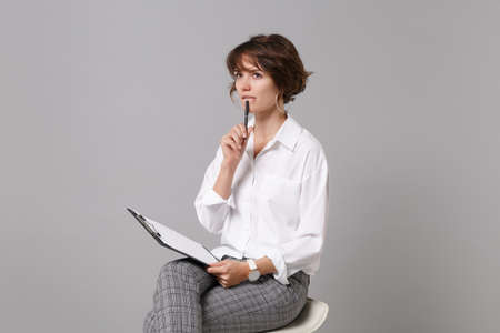 Pensive young business woman in white shirt isolated on grey background. Achievement career wealth business concept. Mock up copy space. Hold clipboard with papers document, writing notes, sitting.