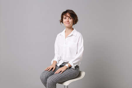 Smiling attractive young business woman in white shirt posing isolated on grey wall background studio portrait. Achievement career wealth business concept. Mock up copy space. Sitting, looking camera.