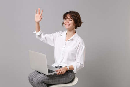 Pleasant young business woman in white shirt isolated on grey background. Achievement career wealth business concept. Hold laptop pc computer, sitting, waving greeting with hand as notices someone. Stock fotó