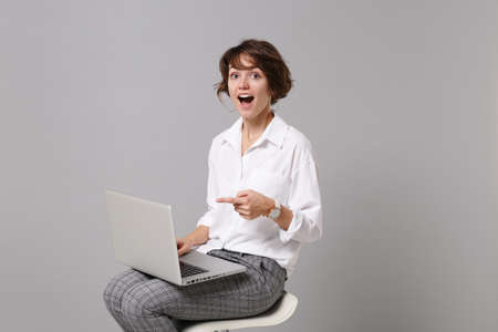 Excited young business woman in white shirt isolated on grey background in studio. Achievement career wealth business concept. Mock up copy space. Pointing index finger on laptop pc computer, sitting.