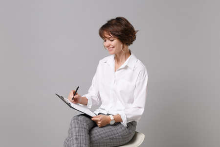 Smiling young business woman in white shirt isolated on grey background. Achievement career wealth business concept. Mock up copy space. Hold clipboard with papers document, writing notes, sitting.