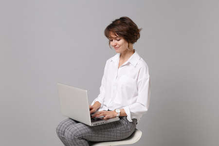 Smiling young business woman in white shirt isolated on grey wall background studio portrait. Achievement career wealth business concept. Mock up copy space. Working on laptop pc computer, sitting. Stock fotó