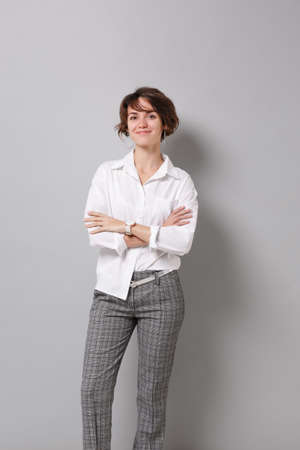 Smiling beautiful young business woman in white shirt posing isolated on grey wall background studio portrait. Achievement career wealth business concept. Mock up copy space. Holding hands crossed.