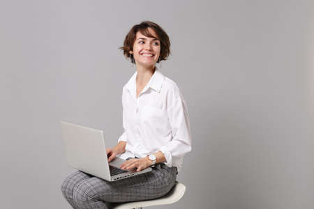 Smiling young business woman in white shirt isolated on grey background in studio. Achievement career wealth business concept. Mock up copy space. Working on laptop pc computer sitting, looking aside.