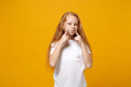 Pretty little ginger kid girl 12-13 years old in white t-shirt isolated on yellow background studio portrait. Childhood lifestyle concept. Mock up copy space. Pointing index fingers on blowing cheeks.