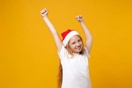 Joyful little ginger kid Santa girl 12-13 years old in white t-shirt Christmas hat isolated on yellow background. New Year 2020 celebration holiday concept. Mock up copy space. Doing winner gesture. Stock Photo