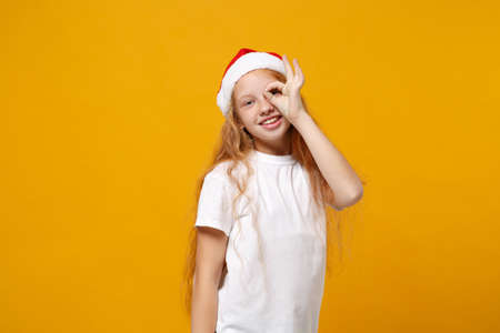 Little ginger kid Santa girl 12-13 years old in white t-shirt Christmas hat isolated on yellow background. New Year 2020 concept. Mock up copy space Hold hand near eye imitating glasses or binoculars.