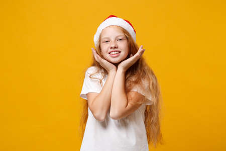 Beautiful little ginger kid Santa girl 12-13 years old in white t-shirt Christmas hat isolated on yellow background. New Year 2020 celebration concept. Mock up copy space. Put hands prop up on chin. Stock Photo
