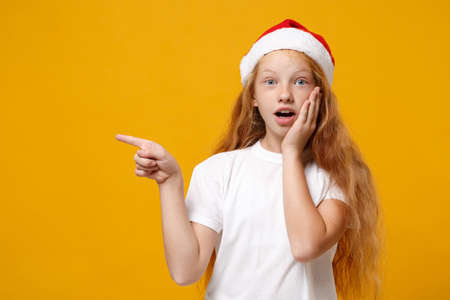 Shocked little ginger kid Santa girl 12-13 years old in white t-shirt Christmas hat isolated on yellow background. New Year 2020 celebration concept. Mock up copy space. Pointing index finger aside.