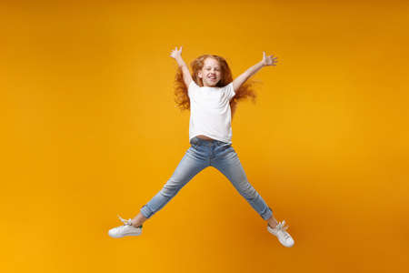 Funny little ginger kid girl 12-13 years old in white t-shirt isolated on yellow background. Childhood lifestyle concept. Mock up copy space. Having fun, fooling around, jumping, spreading hands legs.