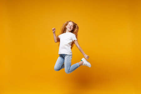 Cheerful little ginger kid girl 12-13 years old in white t-shirt isolated on yellow background children portrait. Childhood lifestyle concept. Mock up copy space. Having fun, fooling around, jumping. Banco de Imagens