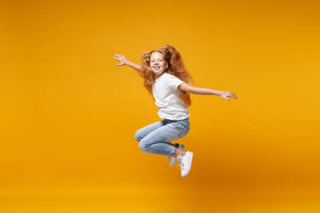 Pretty little ginger kid girl 12-13 years old in white t-shirt isolated on yellow background. Childhood lifestyle concept. Mock up copy space. Having fun, fooling around, jumping, spreading hands.