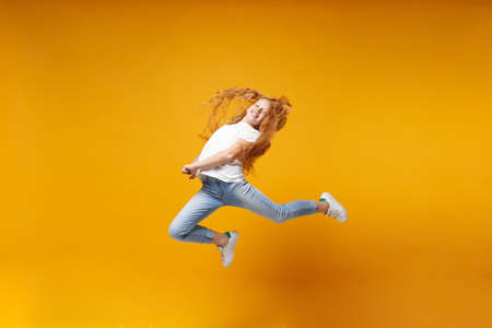 Funny little ginger kid girl 12-13 years old in white t-shirt isolated on yellow background children portrait. Childhood lifestyle concept. Mock up copy space. Having fun, fooling around, jumping.