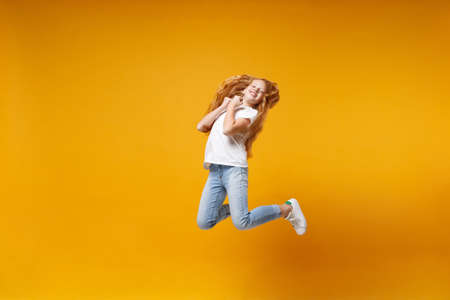 Pretty little ginger kid girl 12-13 years old in white t-shirt isolated on yellow background children portrait. Childhood lifestyle concept. Mock up copy space. Having fun, fooling around, jumping. Foto de archivo