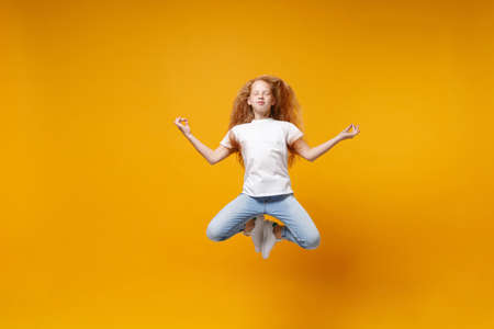 Little ginger kid girl 12-13 years old in white t-shirt isolated on yellow background children portrait. Childhood lifestyle concept. Mock up copy space. Jumping hold hands in yoga gesture meditating.
