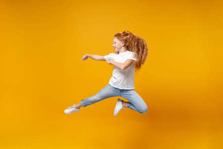 Side view of little ginger kid girl 12-13 years old in white t-shirt isolated on yellow background children portrait. Childhood lifestyle concept. Mock up copy space. Having fun, fooling around, jump.