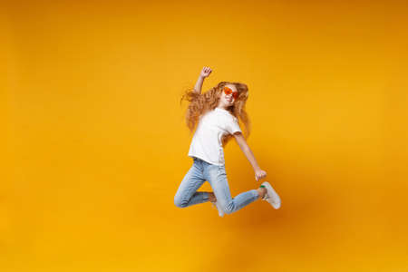 Funny little ginger kid girl 12-13 years old in white t-shirt, heart glasses isolated on yellow wall background. Childhood lifestyle concept. Mock up copy space. Having fun, fooling around, jumping.