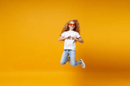 Pretty little ginger kid girl 12-13 years old in white t-shirt, heart glasses isolated on yellow background. Childhood lifestyle concept. Mock up copy space. Jumping, showing shape heart with hands.