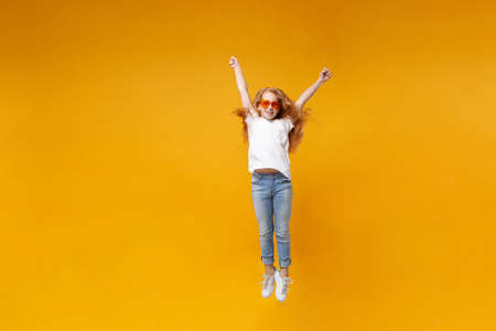 Cheerful little ginger kid girl 12-13 years old in white t-shirt, heart glasses isolated on yellow wall background. Childhood lifestyle concept. Mock up copy space. Having fun, jumping, rising hands.