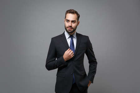 Attractive young bearded business man in classic black suit shirt tie posing isolated on grey background studio portrait. Achievement career wealth business concept. Mock up copy space. Looking aside.