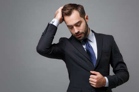 Handsome young business man in classic black suit shirt tie posing isolated on grey background in studio. Achievement career wealth business concept. Mock up copy space. Correcting hair, looking down. Foto de archivo