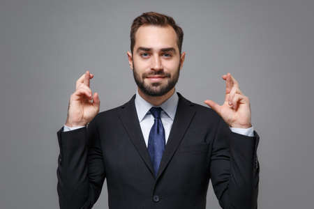Young business man in suit shirt tie posing isolated on grey background. Achievement career wealth business concept. Mock up copy space. Wait for special moment, keeping fingers crossed, making wish.
