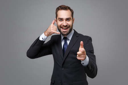 Young business man in suit shirt tie posing isolated on grey background. Achievement career wealth business concept. Mock up copy space. Doing phone gesture like says call me back, point index finger.