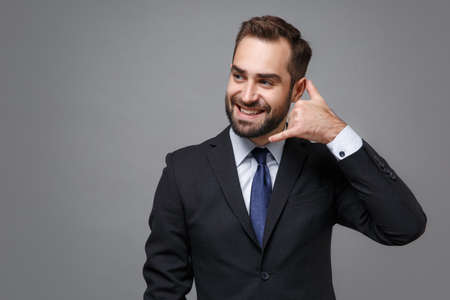Smiling young business man in classic suit shirt tie posing isolated on grey background. Achievement career wealth business concept. Mock up copy space. Doing phone gesture like says call me back.