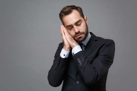 Young bearded business man in classic black suit shirt tie posing isolated on grey wall background. Achievement career wealth business concept. Mock up copy space. Sleep with folded hands under cheek.