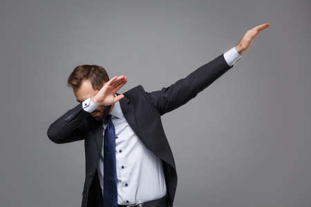 Young bearded business man in classic black suit shirt tie posing isolated on grey background studio portrait. Achievement career wealth business concept. Mock up copy space.Showing DAB dance gesture. Reklamní fotografie