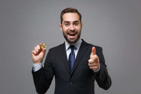 Excited young business man in suit shirt tie posing isolated on grey background. Achievement career wealth business concept. Mock up copy space. Hold bitcoin future currency pointing finger on camera.