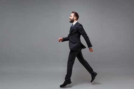Side view of laughing young business man in classic suit shirt tie posing isolated on grey background. Achievement career wealth business concept. Mock up copy space. Running, jumping, looking aside. Imagens