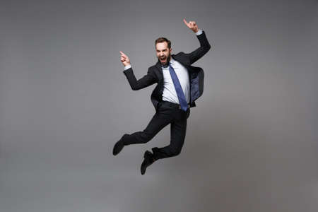 Happy young business man in classic black suit shirt tie posing isolated on grey background. Achievement career wealth business concept. Mock up copy space. Jumping, point index fingers up, screaming.